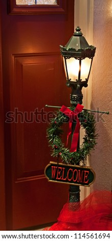 This doorway home Christmas scene is a traditional outdoor lamp post with a welcome sign and wreath.  Inviting guests to enter in for holiday cheer. - stock photo