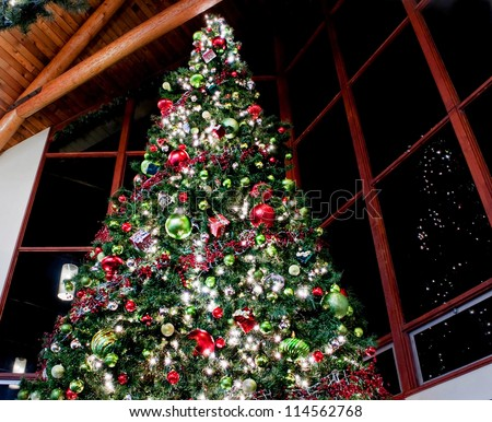 This dramatic image is of a very large indoor Christmas tree with lights, ornaments, balls, square gifts and more reflected against sectioned windows against a night sky. - stock photo