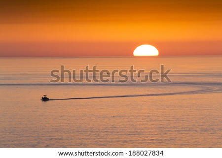 This fishing boat heads home from fishing in front of a beautiful sunset at Clearwater Beach, Florida in the Gulf of Mexico. - stock photo
