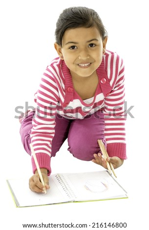 This girl is sitting on the floor and she is writing on her book. - stock photo