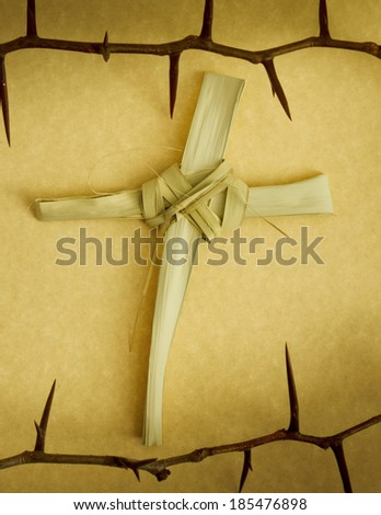 This Handmade Cross of Palm Branch leaves, surround by a Crown of Thorns represents Palm Sunday, Jesus's Good Friday Crucifixion and his rising on Easter Sunday - stock photo