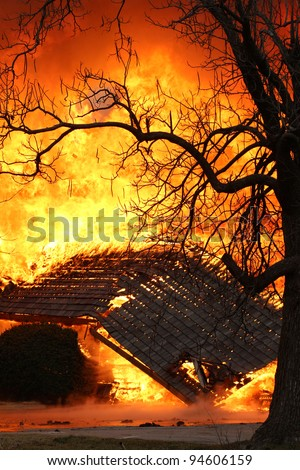 This house fire blazed out of control, burning the structure to the ground. - stock photo