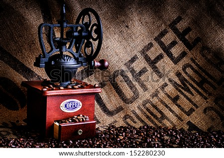 This image is of coffee beans, coffee grinder, and coffee beans bag in background. - stock photo