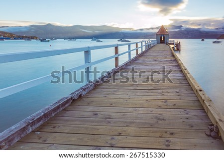 This image shows a pier at sunset in New Zealand - stock photo