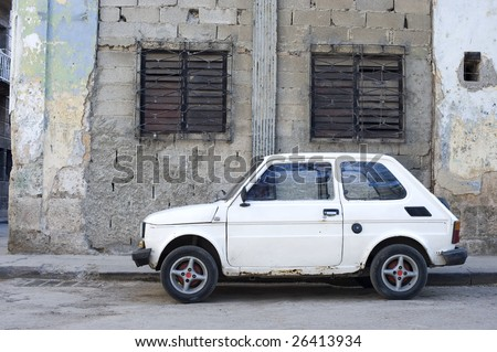 This image shows an old car against the crumbling buildings of Havana, Cuba - stock photo