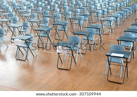 This image shows rows of empty desk waiting for student testing. - stock photo