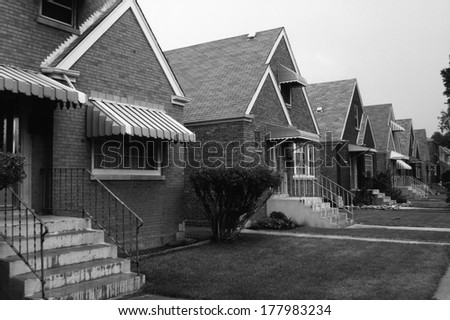 This is a black and white image of a row of single family houses. They are located on the south side of Chicago. They are brick houses with striped awnings over the front window and front door. - stock photo