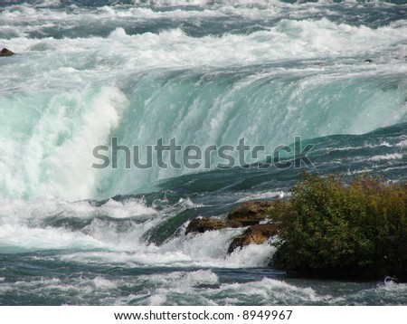 This is a close-up shot of the Niagara River as it goes over the falls. This was shot at Niagara Falls from the Canadian side. - stock photo