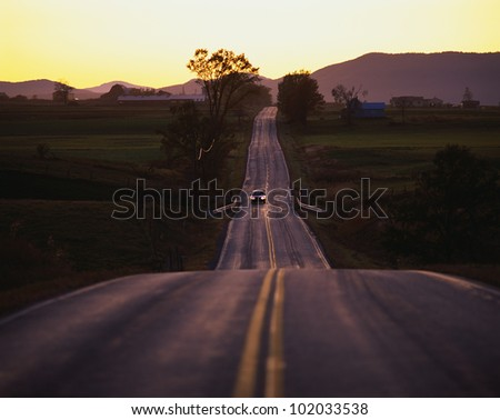 This is a country road at sunset in the Adirondack area. The road trails off into infinity. There is a car coming forward. - stock photo