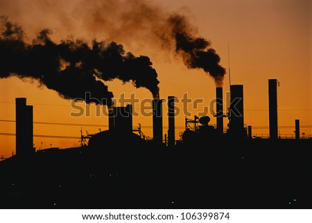 This is a Ford factory at sunset. These are smokestacks contributing to the pollution in the air. - stock photo