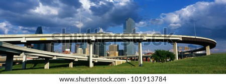This is a freeway overpass with the Dallas skyline visible behind it. The freeway curves and snakes around in a circle in front of the city. - stock photo
