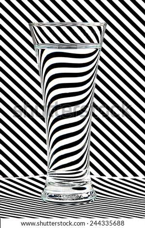 This is a glass of water shot against a striped background to illustrate the effect of water in refracting light. - stock photo