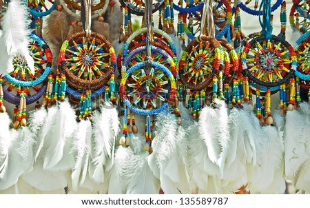 This is a group of Native American beaded dream catchers, with white feathers at the bottom.