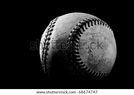 This is a high contrast, black and white shot of an old baseball. Shot on a black background with a hard light source. - stock photo