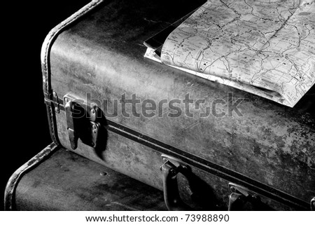 This is a high contrast, black and white shot of an old, beat up suitcase with a map of Montana sitting on top. - stock photo