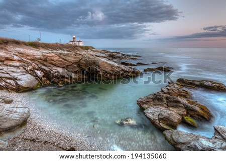 This is a long exposure HDR photo of Beavertail Lighthouse at sunset near Jamestown in Rhode Island, USA. This is a rocky coastal travel seascape. / Beavertail Lighthouse at Night - stock photo