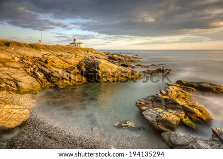 This is a long exposure HDR photo of Beavertail Lighthouse at sunset near Jamestown in Rhode Island, USA. This is a rocky coastal travel seascape. / Beavertail Lighthouse at Sunset. - stock photo
