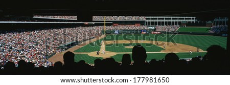 This is a major league baseball game being played at The Ballpark. The teams are the Texas Rangers vs. Baltimore Orioles. In the foreground are fans sitting down in silhouette.