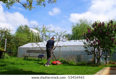 This is a men mowing the grass. - stock photo