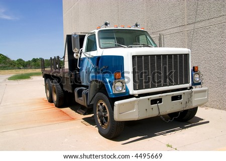 This is a mid 1980's heavy duty flatbed truck viewed from the front corner. - stock photo