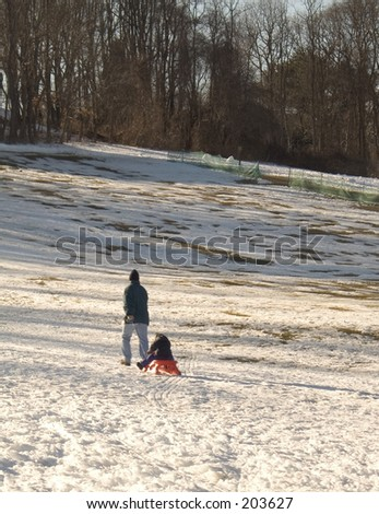 This is a photo of a dad pulling his child back up the hill on a sled.