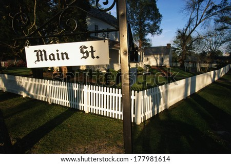 This is a photo of a typical suburban house on Main Street, USA. There is a white picket fence on a shaded, tree lined street with a green lawn. The corner has sign saying Main Street & Front Street. - stock photo