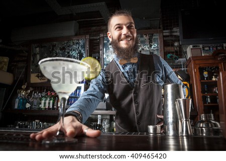 This is a photograph of barman serving cocktail margarita. - stock photo