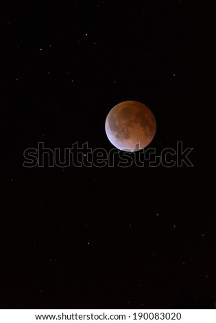 This is a photograph of the Lunar Eclipse Blood Moon moving out of its maximum stage at 3:00 am Central Time. Background star field added from same sky location later.