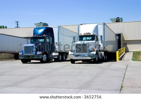 This is a picture of 18 wheeler semi trucks loading at a warehouse building.