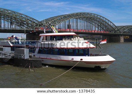 This is a quay view of Rhine river and Hohenzollern railway bridge in Cologne, Germany - stock photo