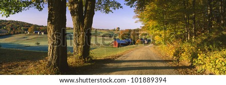 This is a road leading past a farm. - stock photo