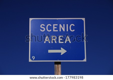 This is a road sign that says, Scenic Area, with a white arrow pointing to the right. The sign has a blue background and is against a blue sky. - stock photo