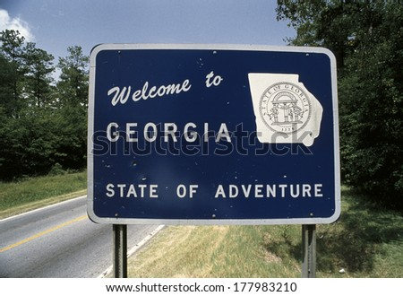 This is a road sign that says, welcome to Georgia, state of adventure. There is a white map of the state of Georgia on its right. There are green bushes on the sign's right and left. - stock photo