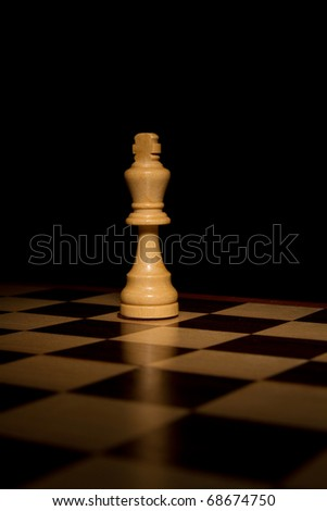 This is a shot of a king chess piece shot alone on a chess board with a shallow depth of field and hard light. - stock photo