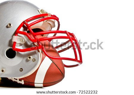 This is a shot of an old scratched up football helmet with a football inside of it. Shot with high contrast on and isolated white background. - stock photo