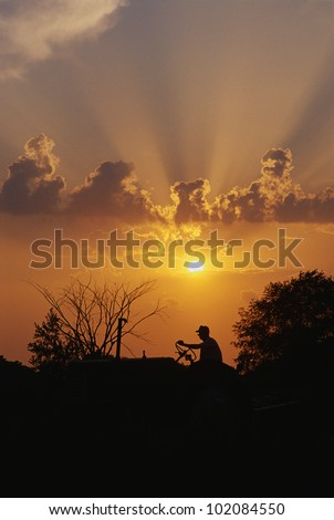 This is a silhouetted farmer on a tractor in the Midwest. It shows rural farming at sunset. - stock photo
