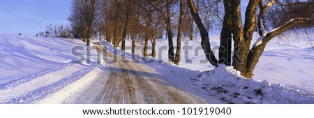 This is a snowy road at sunrise. It shows Winter in New England. - stock photo