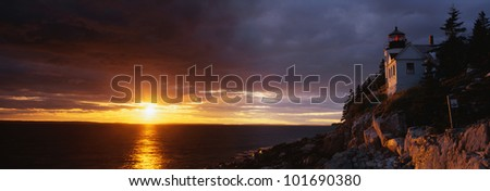 This is a soothing sunset over a serene lighthouse. - stock photo