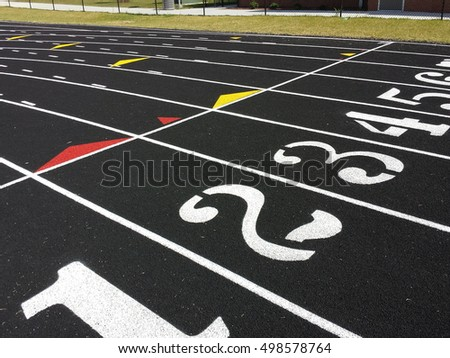 This is a start or finish line on a high school black asphalt race track with eight white numbered lanes and directional arrows.