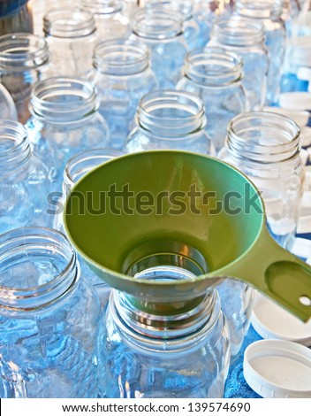 This is a still life of clean canning jars in quart size with a green funnel in preparation for loading fruits or vegetables in to home can.