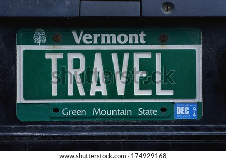 This is a vanity license plate that says TRAVEL. It is a green Vermont license plate. Vermont is the Green Mountain State. - stock photo