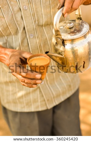 This is a vertical closeup of a man holding a clay cup of masala chai and a tea kettle. This was shot at a roadside chai stand in the countryside of Rajasthan, India. - stock photo