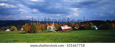 This is a view of a village in autumn. There is a typical New England white church with a tall steeple and a red barn. - stock photo