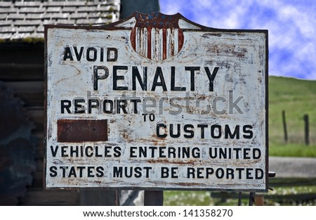 This is a vintage, turn of the century sign of the United States custom, border crossing.  Background is a vintage building and tools. - stock photo