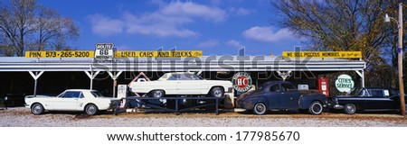 This is a vintage used car dealer along Route 44. It is the former Old Route 66. It is a true piece of Americana. There is a vintage Mustang and a white vintage car on top of a flatbed. - stock photo