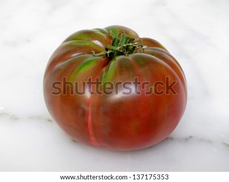 This is a whole, red heirloom tomato sitting on a white marble counter top, just waiting to be cut into.