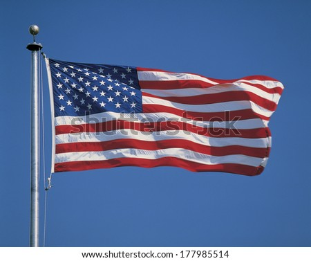 This is an American flag on a flagpole, waving in the wind. - stock photo