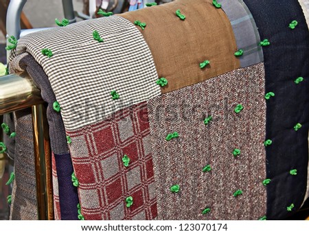 This is an antique quilt hanging on a brass quilt rack.   It's very old and made of brown and neutral tones, and is a tied block style. - stock photo