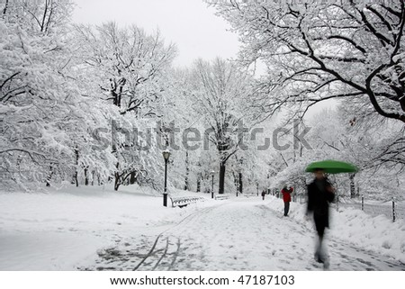 This is an image of a man holding a green umbrella in a snowstorm. - stock photo