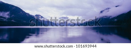 This is an image of the Olympic Peninsula with Crescent Lake in the foreground. The mountains in the background are covered with low altitude clouds. The sky is overcast with clouds. - stock photo